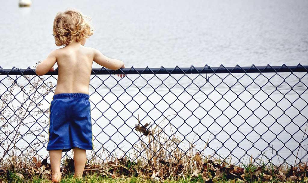 Young-boy-standing-infront-of-a-lake